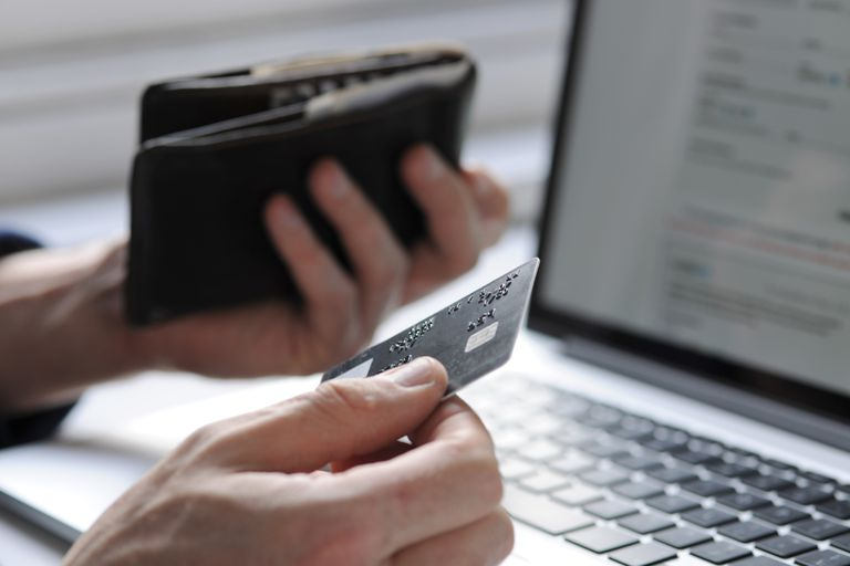 a person holding a credit card in one hand and a wallet in another in front of a laptop