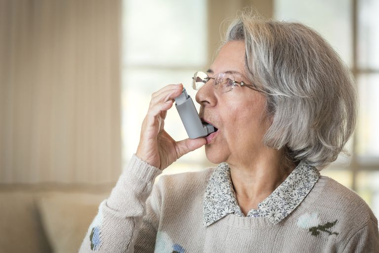 Close up of older Hispanic woman using asthma inhaler