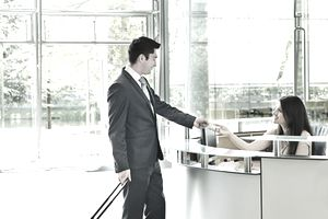 Businessman giving receptionist his credit card