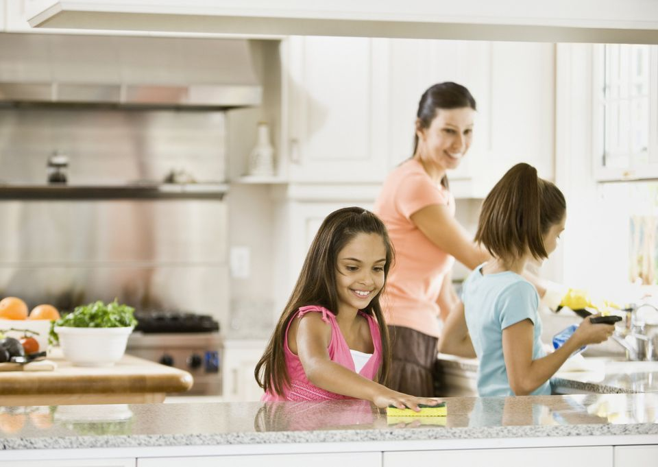 A picture of a family cleaning the kitchen together