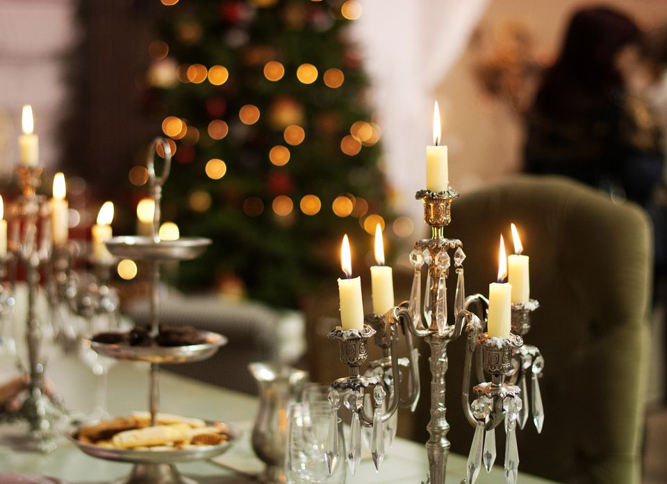 Beautiful romantic Christmas table setting with candles and a Christmas tree
