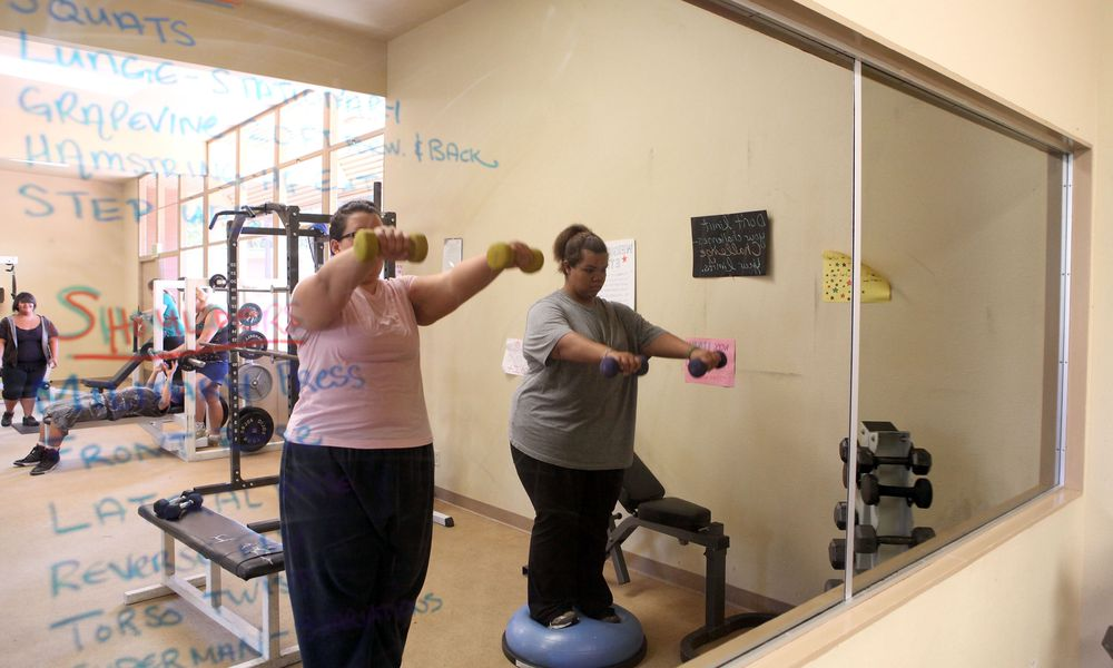 2 overweight women lifting weights