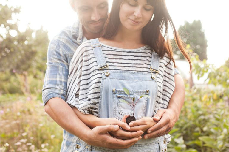 Couple hugging and looking at seedling