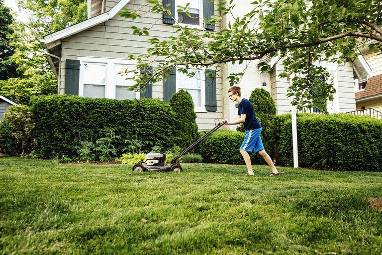 Caucasian boy mowing front lawn
