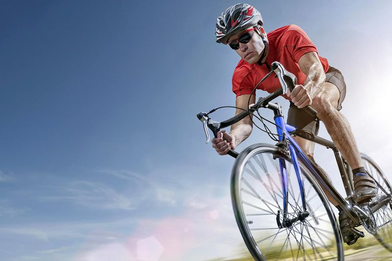 Male cyclist dressed in cycling shorts and helmet riding on road on summer day with intentional motion blur and lens flare.