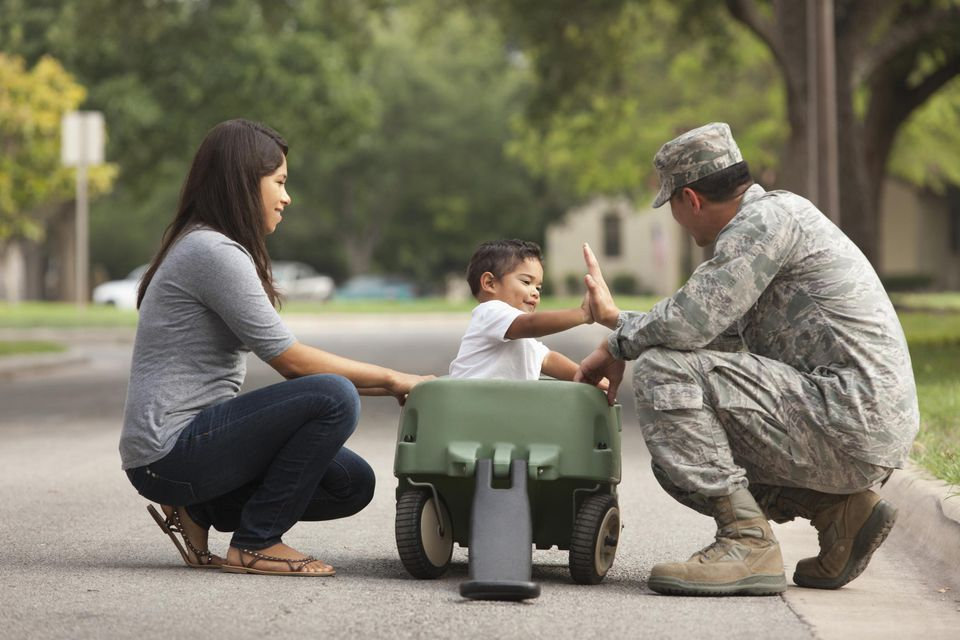 Soldier playing with family on suburban street