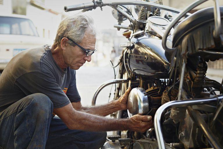 Older man examining motorcycle