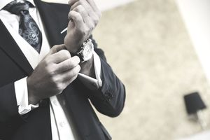 Businessman or groom getting dressed