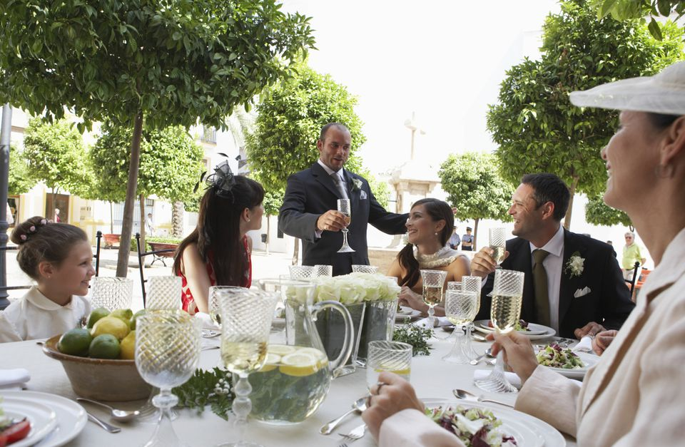Man standing to toast bride and groom at dinner table, outdoors