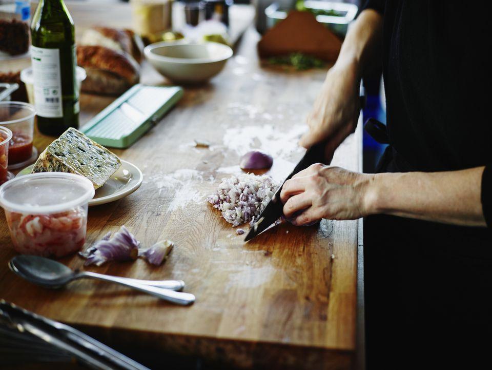 Woman chopping onion on kitchen counter