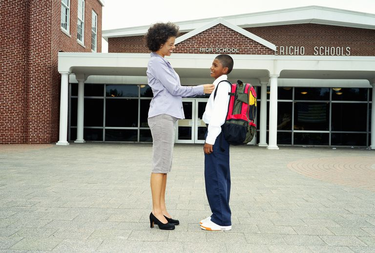 Mother adjusting son's collar outside school, smiling, side view