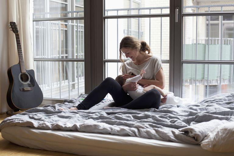 Mother breastfeeding baby girl in bedroom
