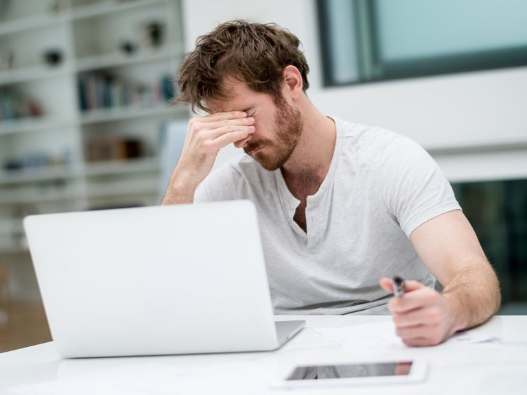 Designer holding head in front of computer