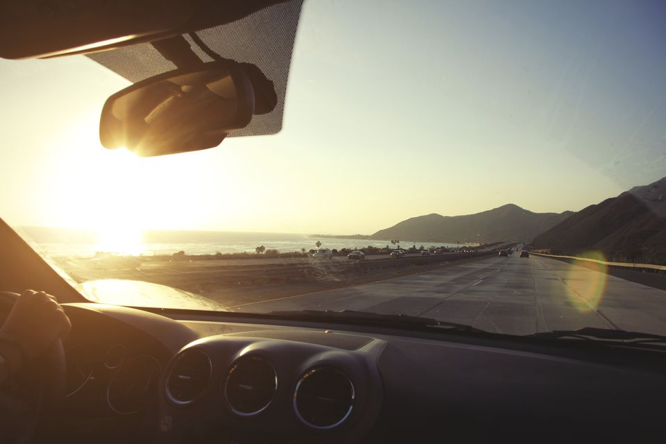 Young woman on the road driving pacific coast highway at sunset, California, USA