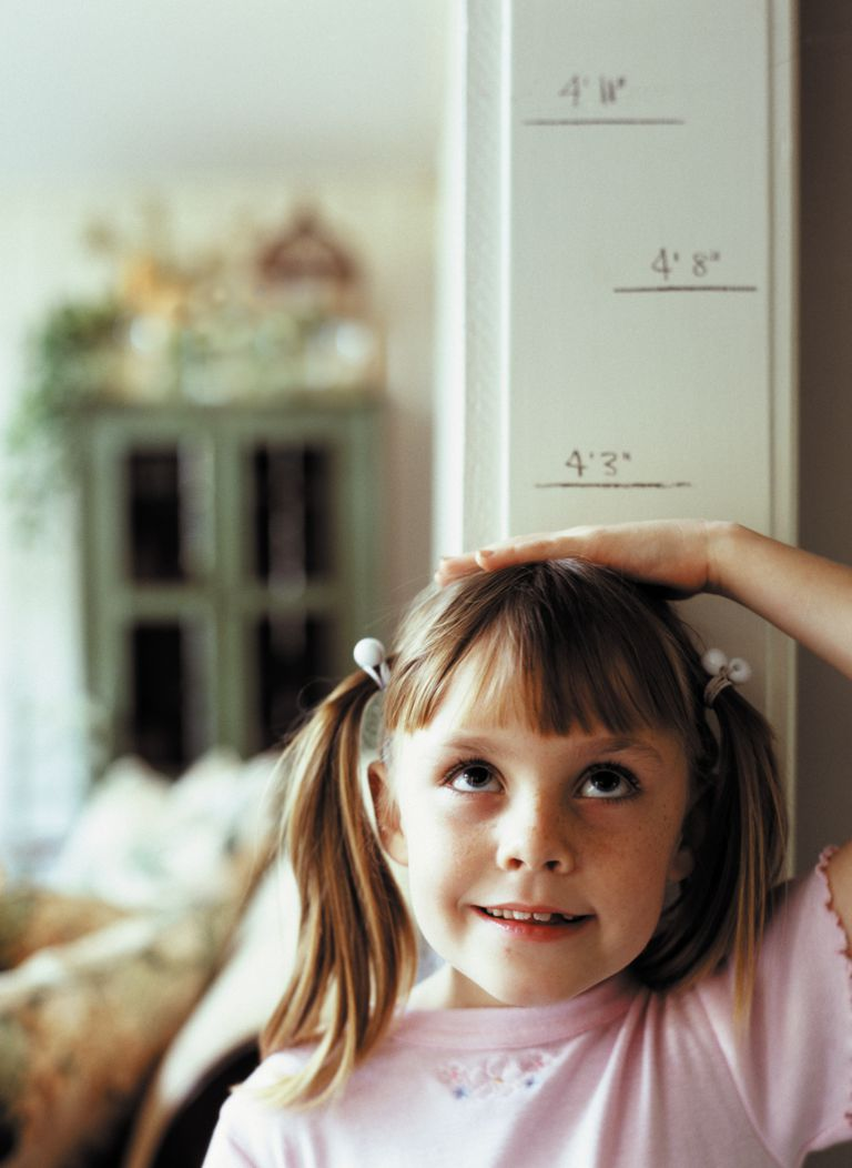 Child measuring her height on the wall.