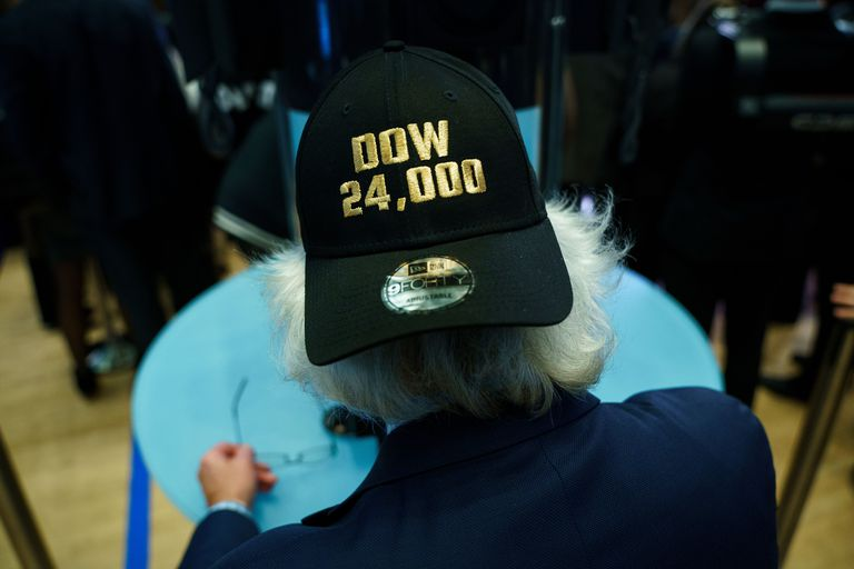 Trader wears hat celebrating Dow record close above 24,000.