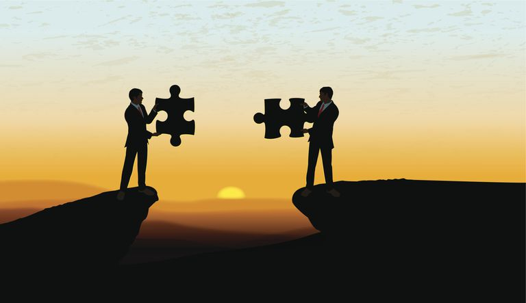 interview questions about career aspirations and plans two businessmen holding puzzle pieces at sunset