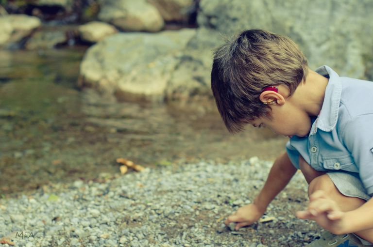 Boy with hearing aid plays next to a creek