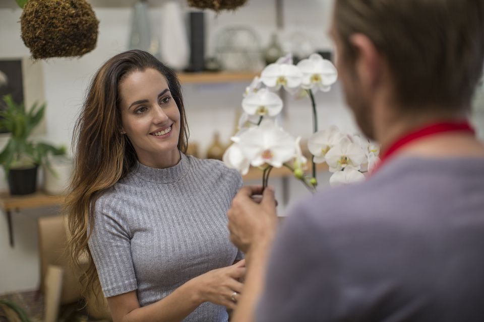 A florist showing orchids to customer