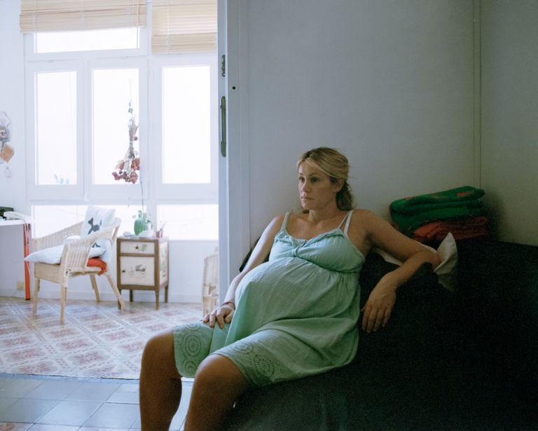 Pregnant woman looks tired as she sits.