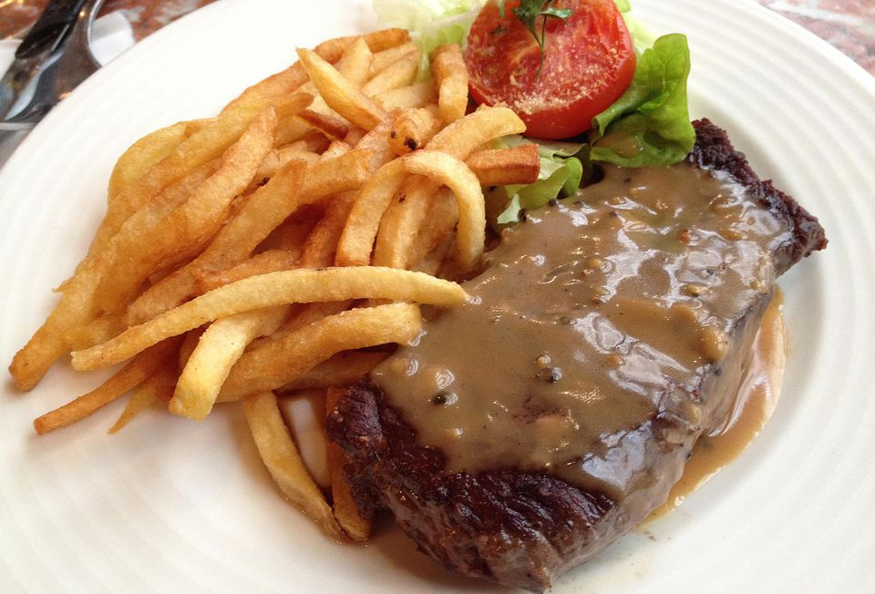 A plate of steak au poivre with fries