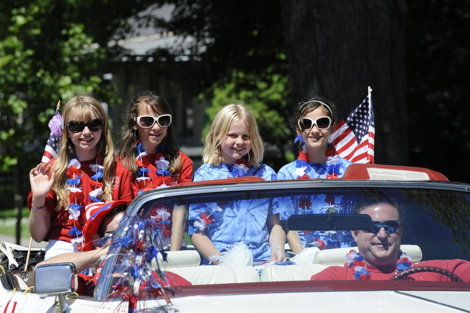 Young girls in open convertible in patriotic parade.