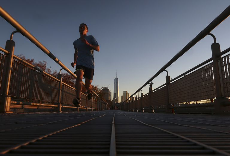 A man runs in the Hudson River Park at sunset in New York City