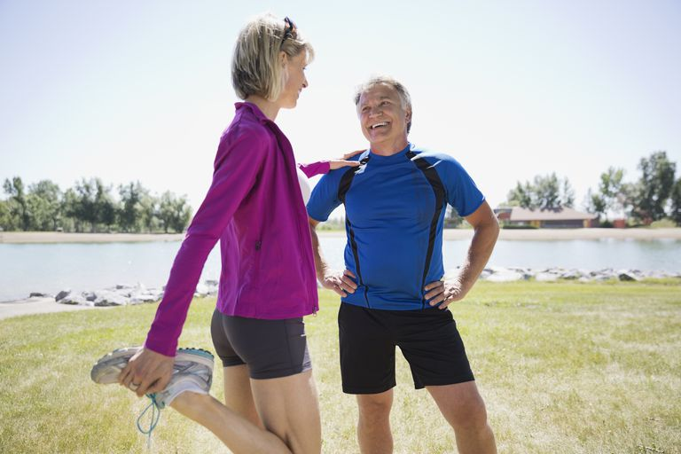 Active middle-aged couple stretching by the beach