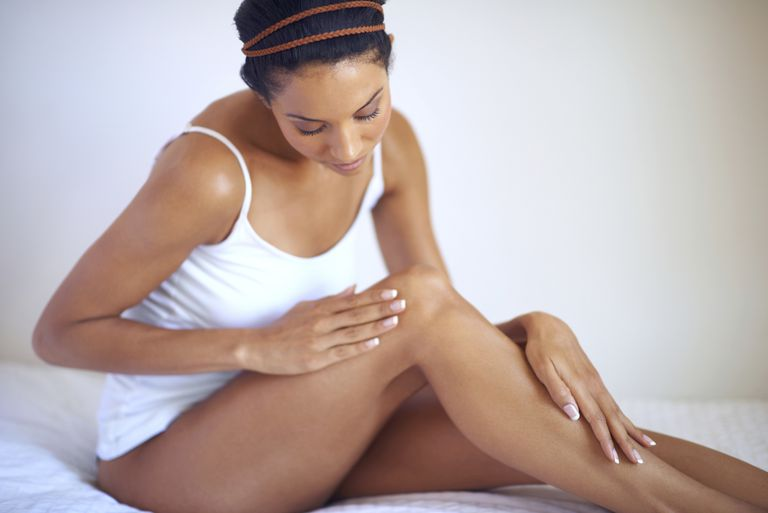 A woman taking care of the skin on her legs.