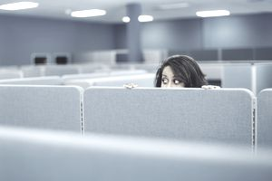 Woman hiding in office cubicle