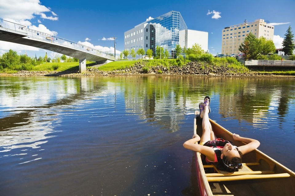A Young Woman Relaxes In A Tandem Canoe While Floating Downstream On The Chena River In Fairbanks, Interior Alaska, Summer