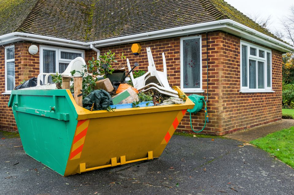 construction dumpster in driveway of home