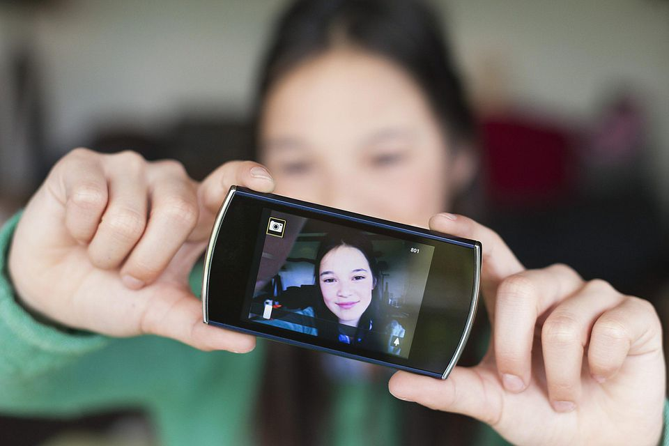 A picture of a child holding up a smartphone