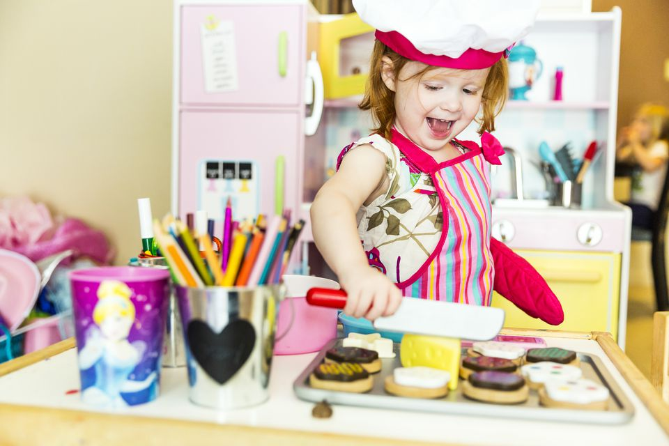 Little Girl Cooking in Toy Kitchen