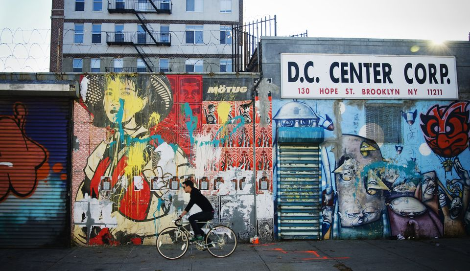Guy riding his bike in front of a wall of graffiti