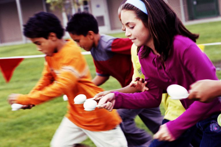 Children (10-12) having spoon and egg race (blurred motion)