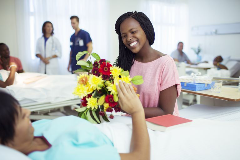 Woman giving mother bouquet of flowers in hospital