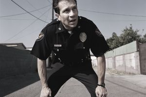 Policeman resting hands on knees, out of breath from running