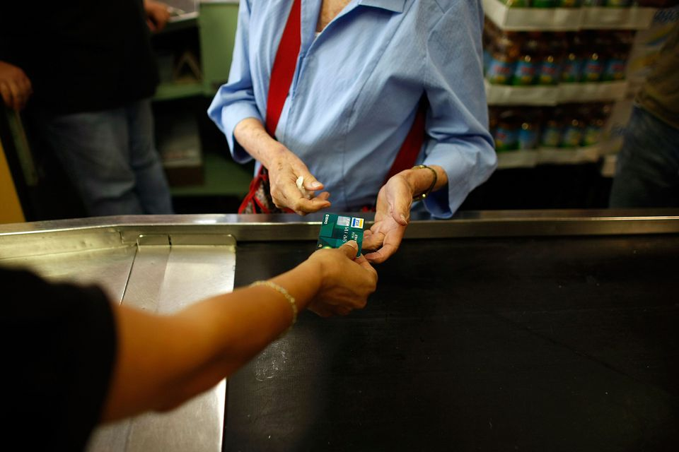 person handing a credit card to a cashier