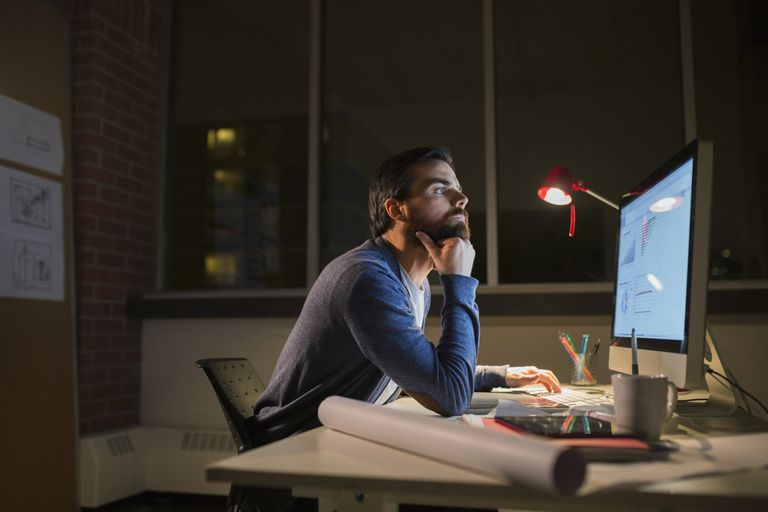 man working at computer in office at night