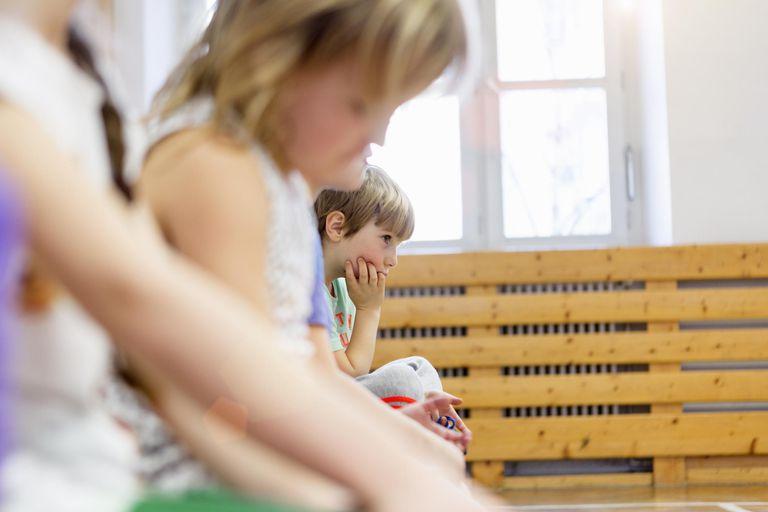 Children sitting on bench in school hall, looking sad