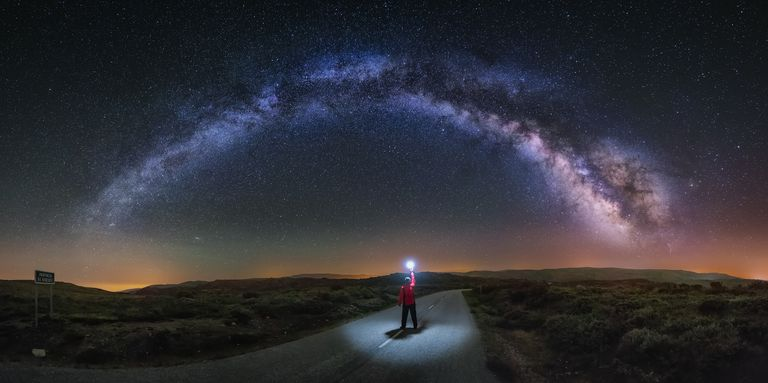 person standing on a road holding a light up to the stars