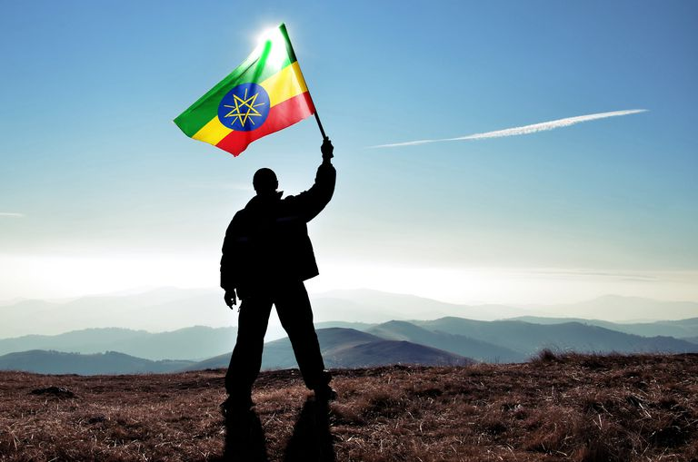 Successful silhouette man winner waving Ethiopian flag on top of the mountain peak