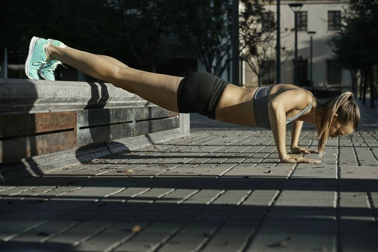 woman doing a decline push up outside