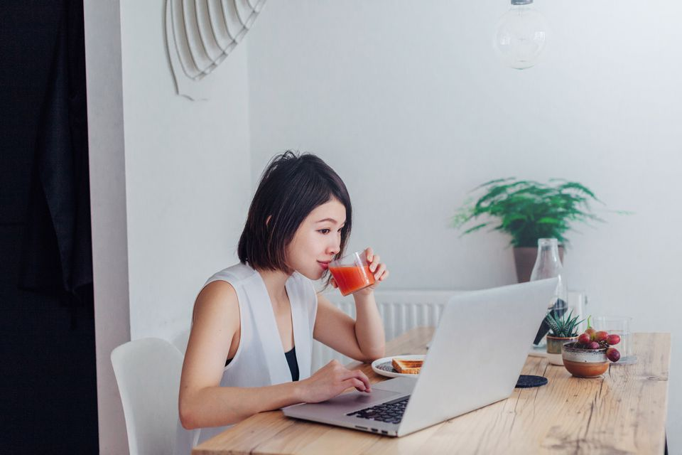Woman using laptop in kitchen while drinking juice