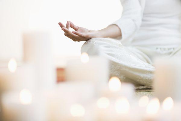 Hispanic woman meditating in lotus position near lit candles
