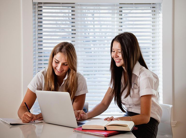 Teen girls doing homework in kitchen