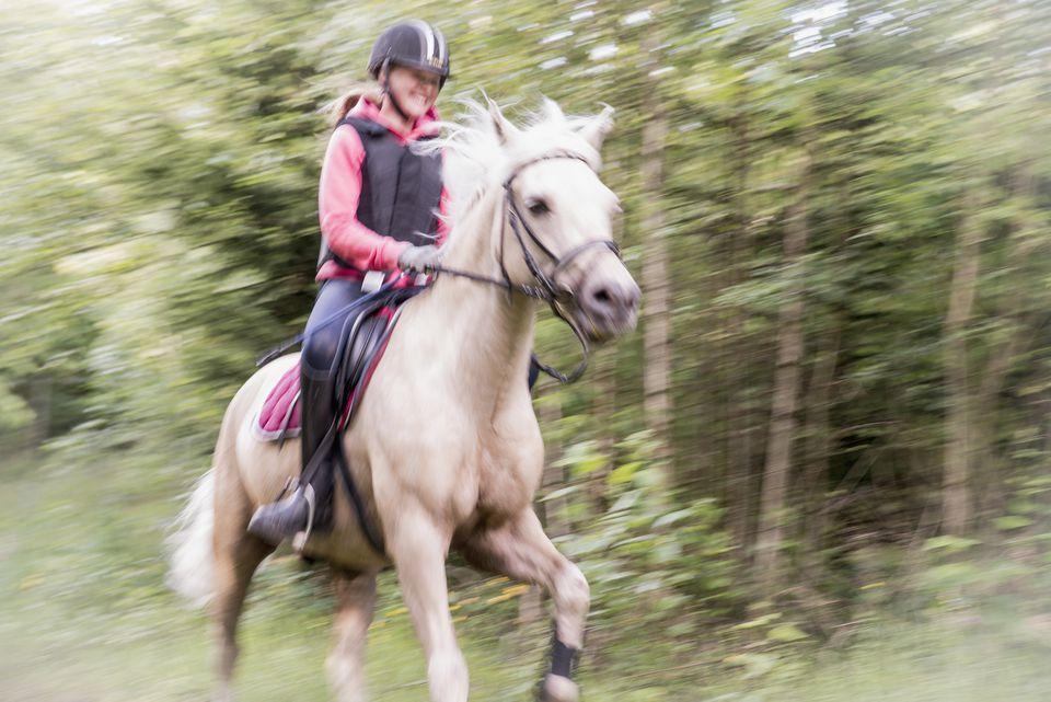Teenage girl riding horse