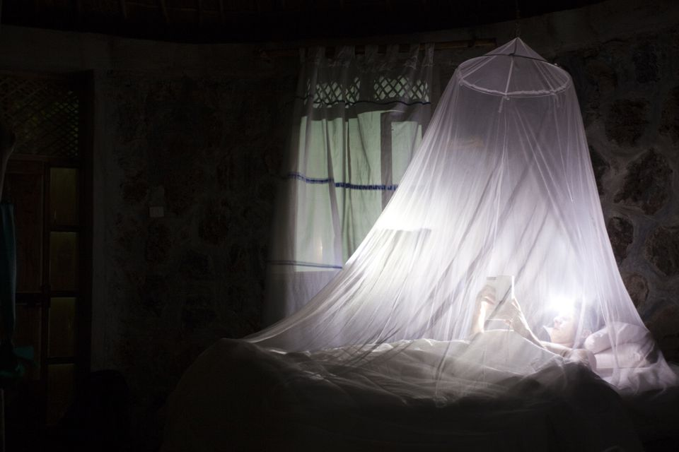 A young man sleeps inside a mosquito net at an ecolodge in Ethiopia.