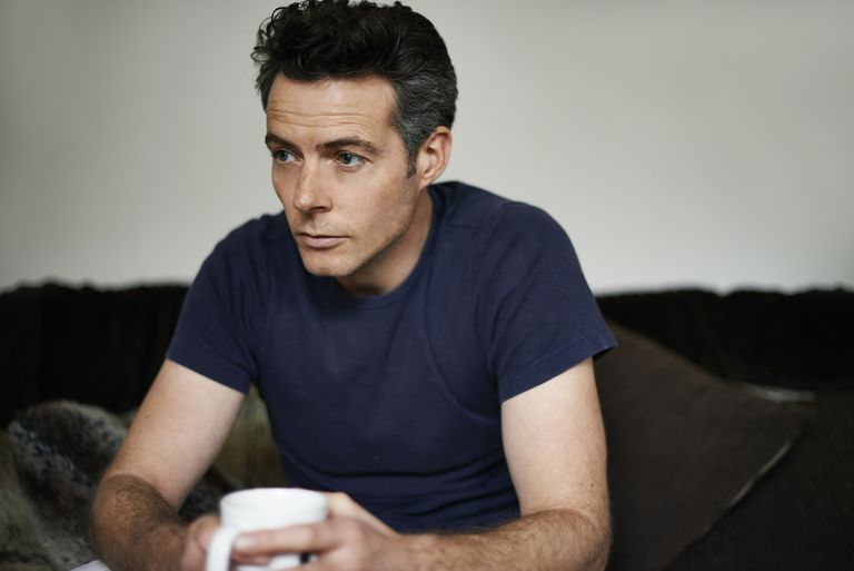 Man sitting on sofa holding mug looking sad